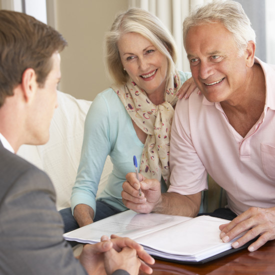 Senior Couple Meeting With Financial Advisor At Home And Smiling